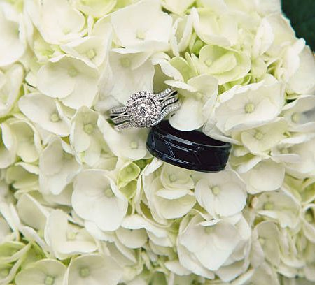 A close up image of wedding bands in a bouquet of hydrangeas.