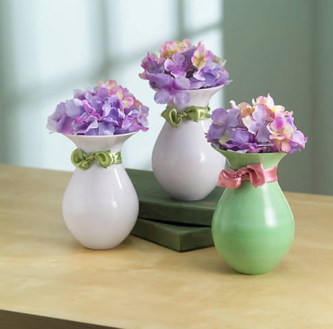 3 Hydrangea blooms in small vases in home environment.  Flowers are imitation but very convincing.