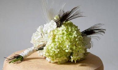 A modern bridal bouquet complete with peacock feathers